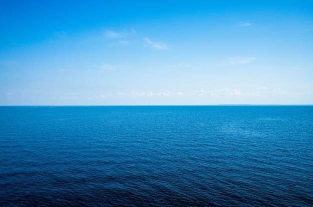 Spokojny minimalistyczny krajobraz z gładką, błękitną powierzchnią morza ze spokojną wodą i czystym niebem