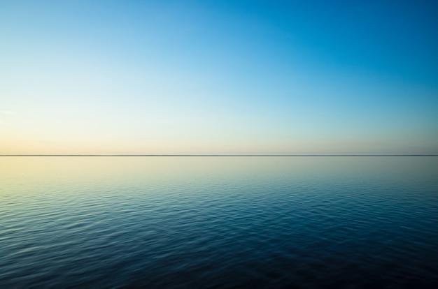 Spokojny minimalistyczny krajobraz z gładką, błękitną taflą morza ze spokojnymi wodami z horyzontem i czystym niebem