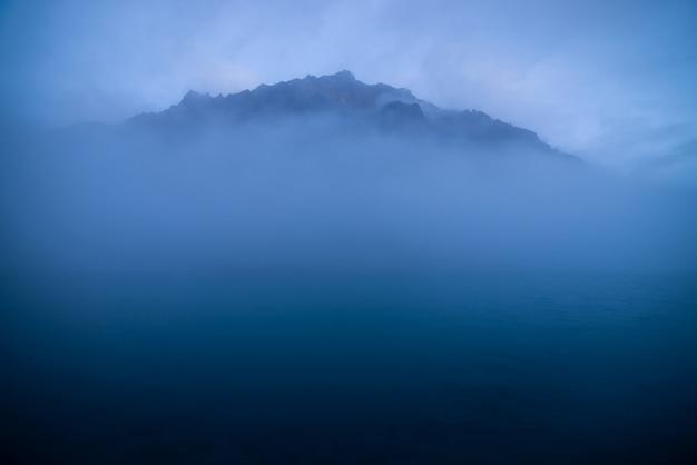 Spokojny minimalny krajobraz z dużą skalistą górą pośrodku wody wśród niskich chmur o zmierzchu. faliste morze w klasycznym niebieskim kolorze. atmosferyczna sceneria z ciemnoniebieskim spokojnym jeziorem i skałą w gęstej mgle.
