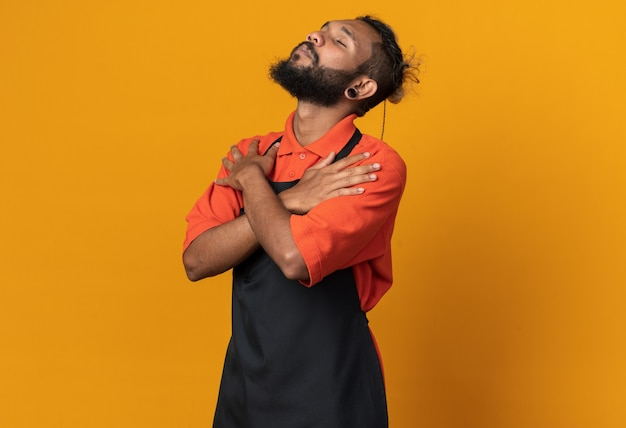 Spokojny młody afroamerykański męski fryzjer ubrany w mundur trzymający ręce skrzyżowane na ramionach z zamkniętymi oczami odizolowanymi na pomarańczowej ścianie z miejscem na kopię