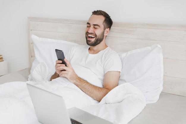 Spokojny młody brodaty mężczyzna leżący w łóżku z białym prześcieradłem na poduszkę w sypialni w domu