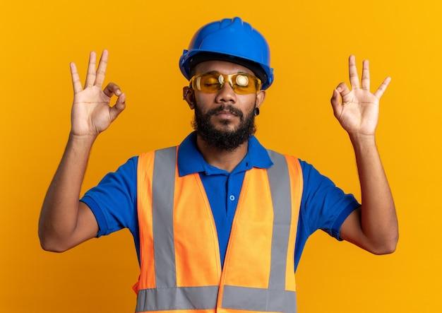 Spokojny młody budowniczy mężczyzna w okularach ochronnych ubrany w mundur z hełmem ochronnym, udający, że medytuje na białym tle na pomarańczowej ścianie z miejscem na kopię