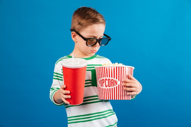 Spokojny młody chłopak w okularach przygotowuje się do obejrzenia filmu