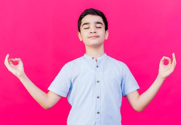 Spokojny młody chłopiec kaukaski medytuje z zamkniętymi oczami na białym tle na szkarłatnym tle