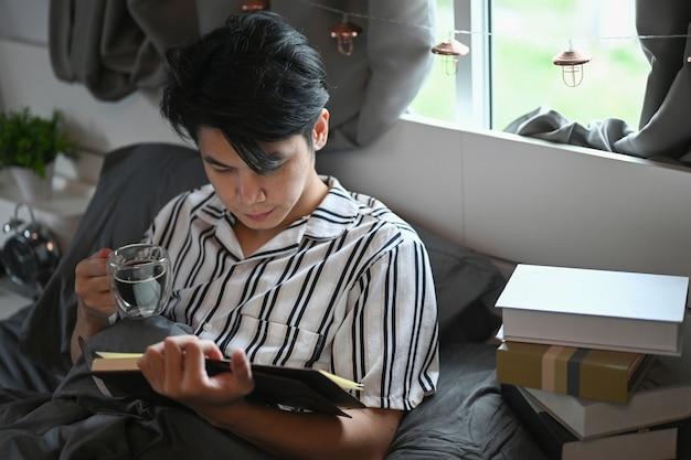 Spokojny młody człowiek pije kawę i czyta książkę na łóżku.