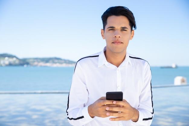 Spokojny młody człowiek używa smartphone