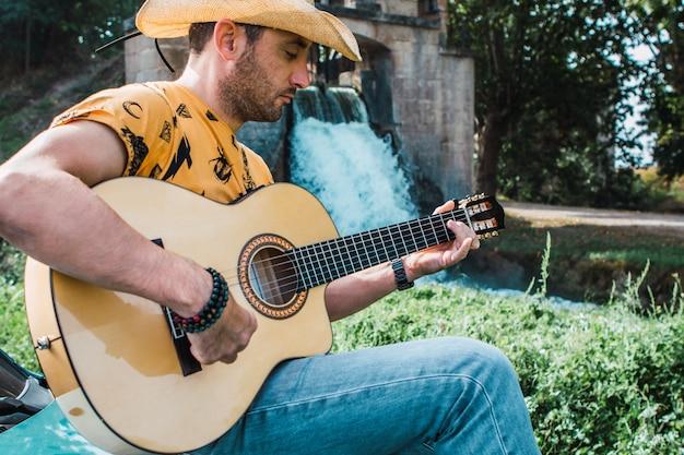 Spokojny młody człowiek z kowbojskim kapeluszem, grający na gitarze w naturalnym otoczeniu