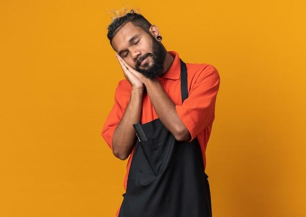 Spokojny młody fryzjer ubrany w mundur wykonujący gest snu na pomarańczowej ścianie z miejscem na kopię