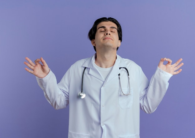Spokojny młody lekarz mężczyzna ubrany w szlafrok i stetoskop medytuje z zamkniętymi oczami na białym tle na fioletowej ścianie