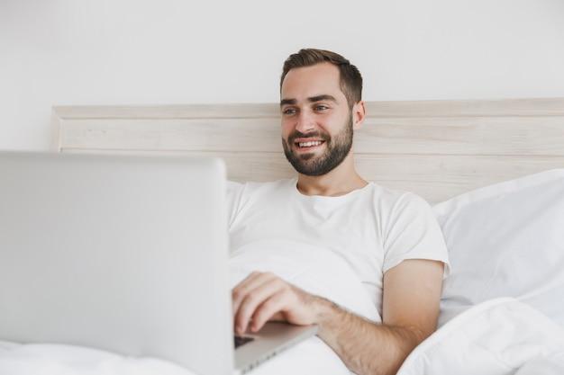 Spokojny młody przystojny brodaty mężczyzna leżący w łóżku z białym prześcieradłem na poduszkę w sypialni w domu