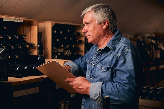 Spokojny, pewny siebie sommelier kaukaski w dżinsowej koszuli stojący ze schowkiem przed półką z rzędami butelek wina