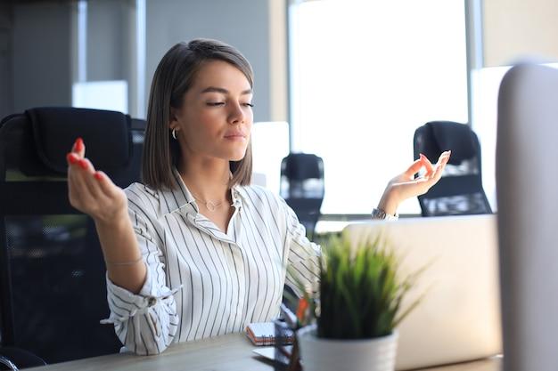 Spokojny piękny bizneswoman praktykowania jogi w pracy, medytując w biurze z zamkniętymi oczami.