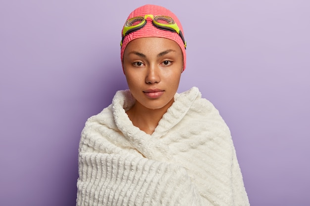 Spokojny pływak suszy się białym miękkim ręcznikiem, ogrzewa po ćwiczeniu stylu grzbietowego, nosi okulary i czepek pływacki, poprawia umiejętności, ma mokrą skórę, izoluje na fioletowej ścianie, utrzymuje kondycję