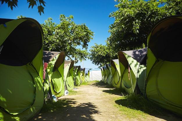 Spokojny poranek w obozie surfingowym z identycznymi zielonymi i czarnymi namiotami w pobliżu plaży