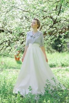 Spokojny portret pięknej kobiety w kwiat jabłoni. zmysłowy portret dziewczyny boho w nowoczesnej kwiecistej sukni w zieleni. miejsce na tekst