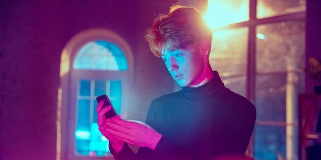 Spokojny, poważny. kinowy portret stylowego redhair mężczyzny w oświetlonym neonami wnętrzu. stonowane jak efekty kinowe w fioletowo-niebieskim kolorze. kaukaski model za pomocą smartfona w kolorowych światłach w pomieszczeniu. ulotka.