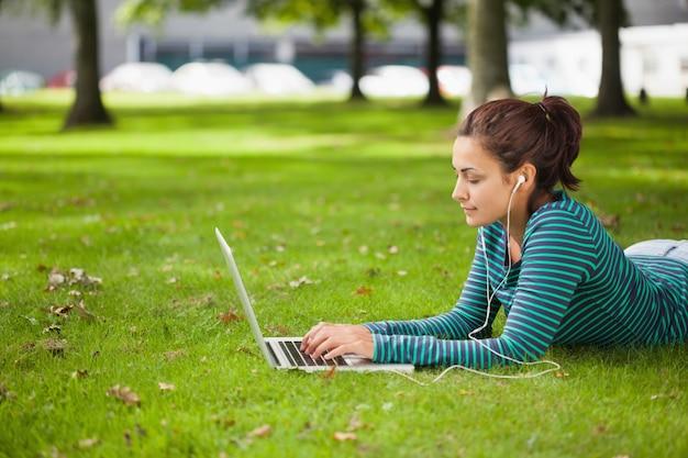 Spokojny przypadkowy studencki lying on the beach na trawie używać laptop