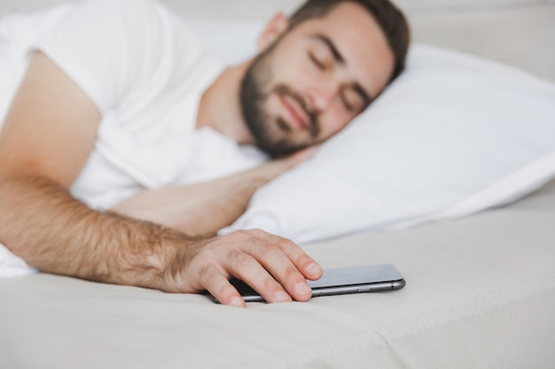 Spokojny przystojny brodaty mężczyzna leżący w łóżku z białym prześcieradłem na poduszkę w sypialni w domu