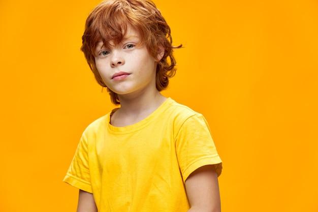 Spokojny rudy chłopiec w żółtej koszulce na białym tle przycięty widok