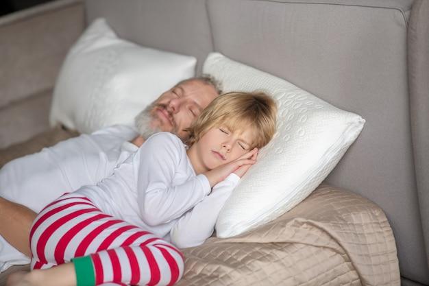 Spokojny sen. spokojne dziecko z tatą, leżące na białych poduszkach na łóżku, śpiące w domu w ciągu dnia