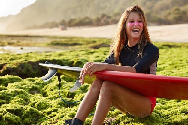 Spokojny, śmiejący się wooman czuje się odprężony, gdy pozuje na zielonej ziemi w pobliżu brzegu morza, trzyma deskę surfingową