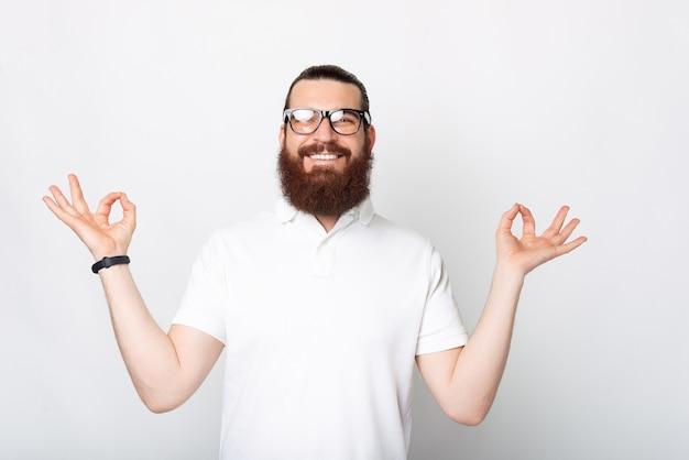 Spokojny, uśmiechnięty mężczyzna patrzy na aparat szczęśliwy w pozie zen w pobliżu białej ściany