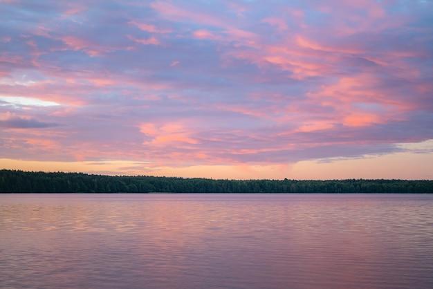 Spokojny wieczór nad jeziorem z płonącym niebem i lasem na powierzchni.
