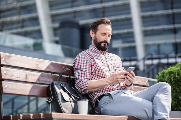 Spokojny wypoczynek. przyjemny przystojny mężczyzna za pomocą swojego telefonu, odpoczywając na ławce