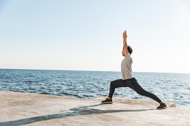 Spokojny zdrowy azjatycki mężczyzna robi ćwiczenia jogi na plaży, balansując