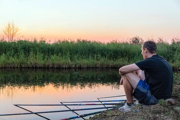 Spokojny, zrelaksowany mężczyzna łowi ryby na wielu łowiskach, siedząc na brzegu jeziora o zachodzie słońca