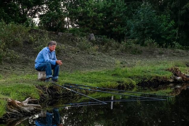 Spokojny, zrelaksowany starszy mężczyzna łowi ryby na wędki siedząc na brzegu jeziora o zachodzie słońca