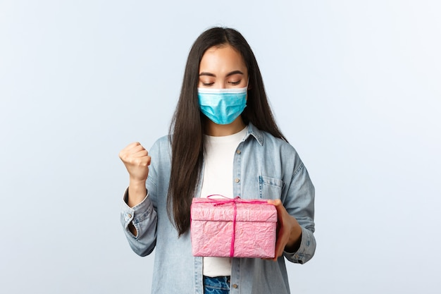 Społeczny dystansowy styl życia, pandemia covid-19, świętowanie wakacji podczas koncepcji koronawirusa. radosna szczęśliwa azjatka otrzymuje prezent, patrząc na pudełko z zadowoloną twarzą, śpiewając, nosząc maskę medyczną.
