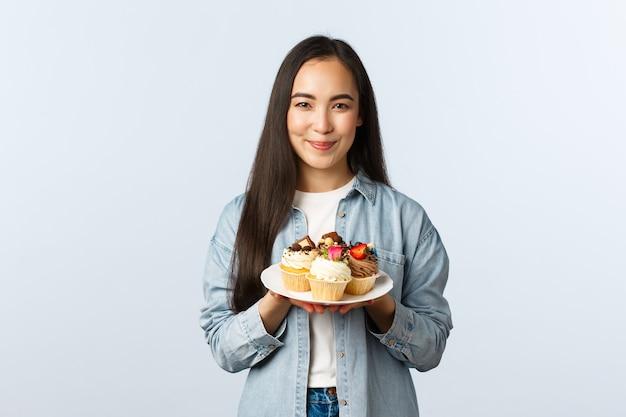 Społeczny dystansowy styl życia, pandemia covid-19, świętowanie wakacji podczas koncepcji koronawirusa. uśmiechnięta właścicielka słodkiej małej kawiarni pokazująca babeczki na talerzu i uśmiechnięta, przygotowana pyszne desery.