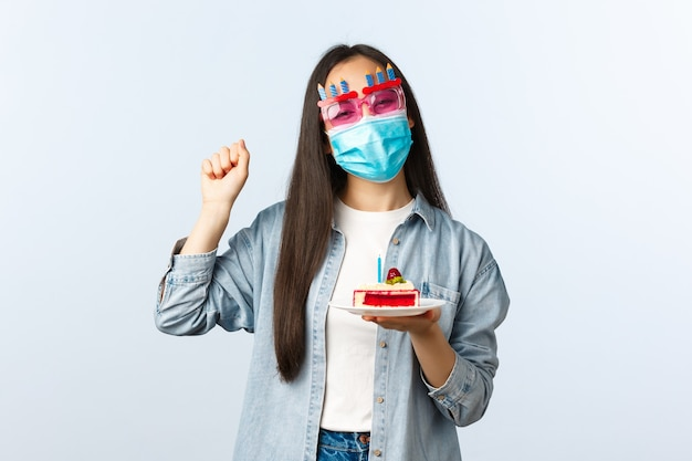 Społeczny dystansowy styl życia, pandemia covid-19, świętowanie wakacji podczas koncepcji koronawirusa. wesoła dziewczyna z okazji urodzin w imprezowych okularach i śpiewanie masek medycznych, przytrzymaj tort urodzinowy.
