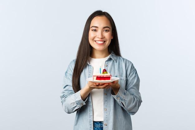 Społeczny dystansowy styl życia, pandemia covid-19, świętowanie wakacji podczas koncepcji koronawirusa. wesoła ładna dziewczyna azjatyckich świętuje urodziny, uśmiechając się trzymając tort urodzinowy ze świecą.