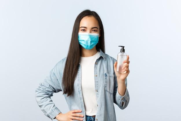 Społeczny styl życia, koncepcja zapobiegania pandemii covid-19. młoda urocza azjatycka kobieta w poradach dotyczących maski medycznej za pomocą środka dezynfekującego do rąk, pokazująca butelkę z mydłem, wyjaśnia środki podczas koronawirusa