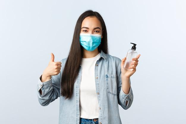 Społeczny styl życia, koncepcja zapobiegania pandemii covid-19. wesoła azjatycka kobieta w masce medycznej pokazuje kciuk w górę, zachęca ludzi do stosowania środka dezynfekującego do rąk i mycia rąk podczas koronawirusa