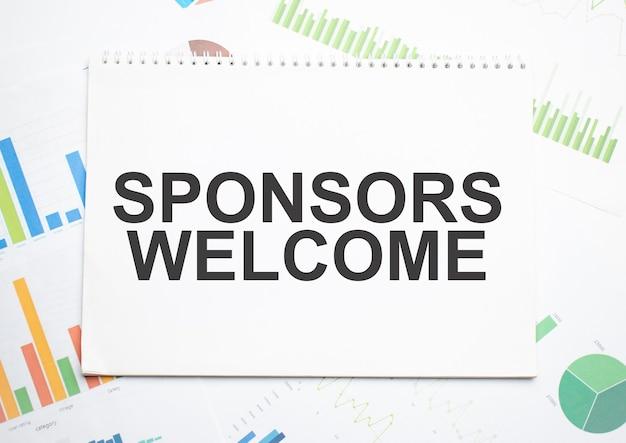 Sponsorzy witamy, etykieta tekstowa w notatniku planowania oraz wykres statystyk. analiza rynku, skuteczna strategia biznesowa.