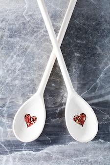 Spoond z dziurkami w kształcie serca i czerwoną przyprawą.