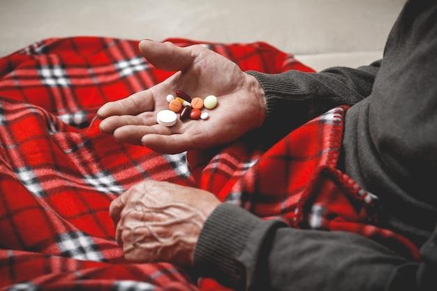 Sporo tabletek w rękach seniora