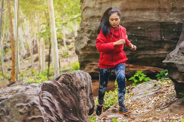 Sport biegnąca kobieta w biegach przełajowych, skacząca na skalistej górskiej ścieżce