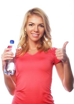 Sport, ćwiczenia i opieka zdrowotna - sportowa blond kobieta z bidonem