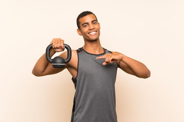 Sport człowiek na izolowane ściany z kettlebell