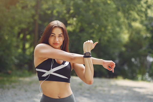 Sport dziewczyna szkolenia ze słuchawkami w parku lato