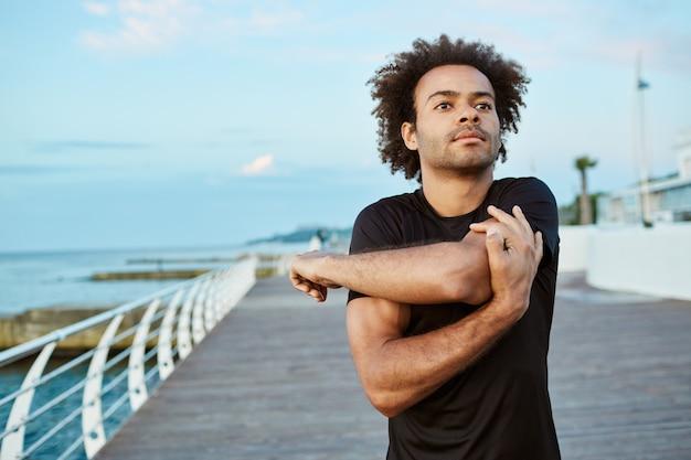 Sport, fitness i zdrowy tryb życia. wysportowany młody afroamerykanin robi rozgrzewkę przed porannym biegiem po promenadzie.
