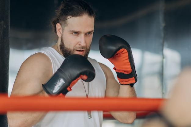 Sport i ludzie, młody sportowiec trenujący w siłowni bokserskiej