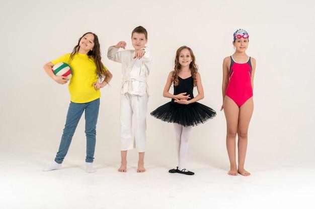 Sport i zajęcia dla dzieci. grupa radosnych chłopców i dziewcząt uprawiających różne sporty, pozujących razem.