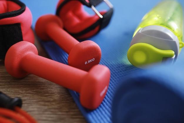 Sport i zdrowy styl życia. akcesoria sportowe. hantle z maty do jogi i skakanka. sportowe tło z koncepcją ćwiczeń domowych.