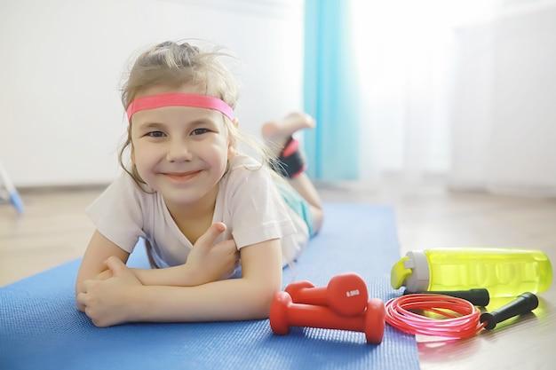 Sport i zdrowy styl życia. dziecko uprawiające sport w domu. hantle z maty do jogi i skakanka. sportowe tło z koncepcją ćwiczeń domowych.