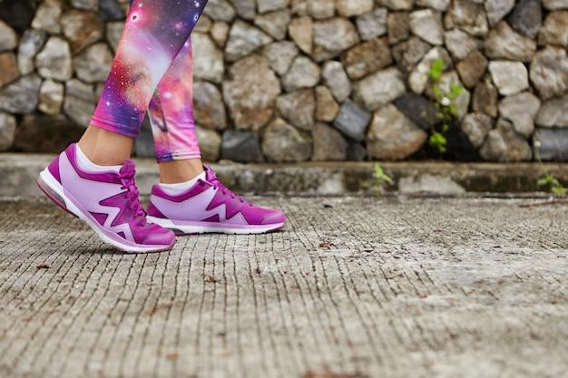 Sport i zdrowy tryb życia. zbliżenie na nogi kobiety w stylowych fioletowych trampkach i legginsach z nadrukiem przestrzeni na chodniku. lekkoatletka stojąc na betonie, ćwiczeń fizycznych w parku miejskim
